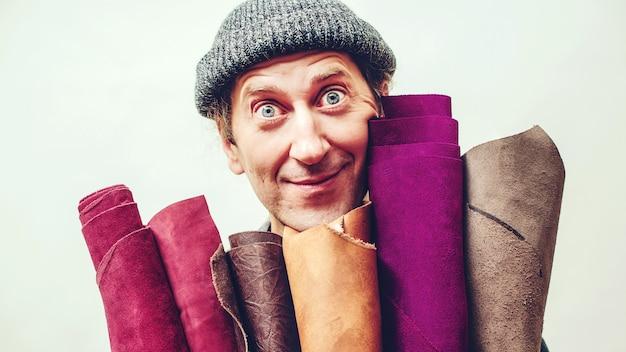 Ремесленник держит набор цветной кожи в своей мастерской. у мастера есть идея для новых кожаных изделий. бизнес и предприниматель концепция.