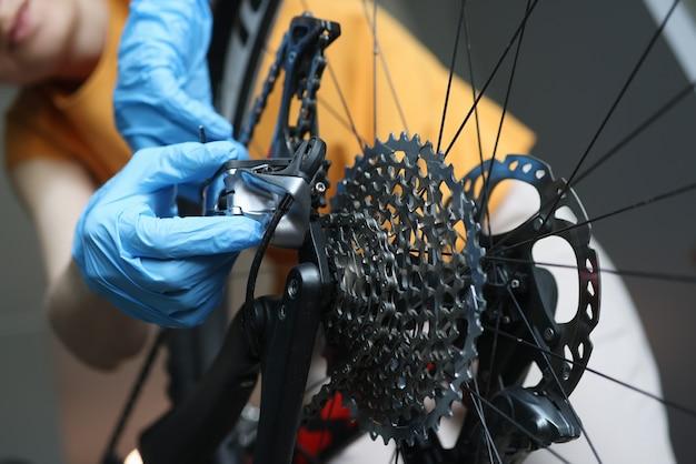 自転車のクローズアップを修理するゴム製保護手袋の職人