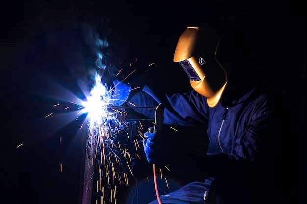 A craftsman is welding with workpiece steel.