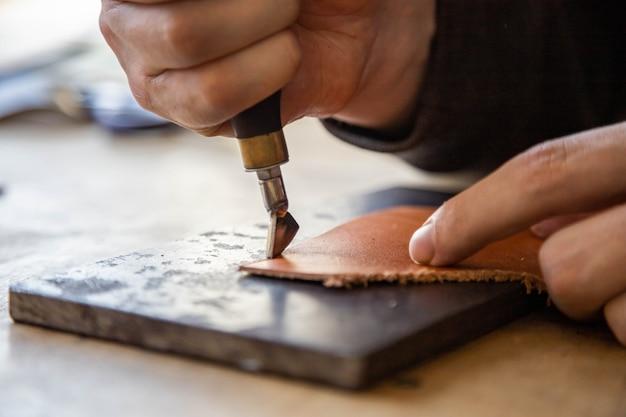 천연 재료 공작물의 장인 기계 가장자리는 전문 곱슬 칼 가죽 워크샵을 사용합니다.