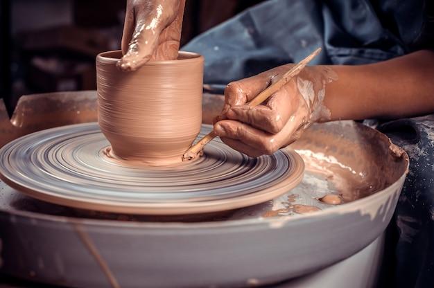 職人のマスター彫刻家は、ろくろの粘土と道具を使ってテーブルで作業します