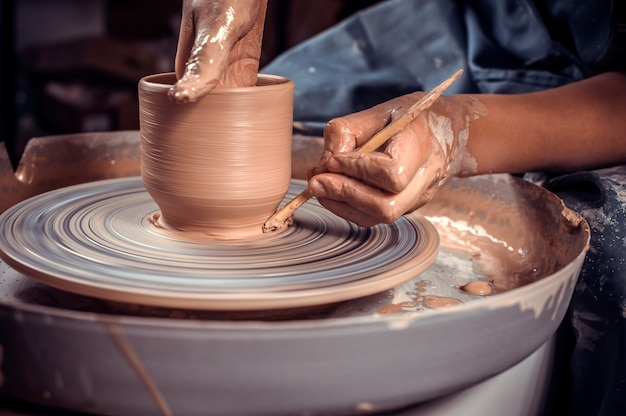 Craftsman master sculptor works with clay on a potter's wheel and at the table with the tools