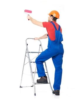 職人の画家がブラシで階段に立って、白の完全な肖像画