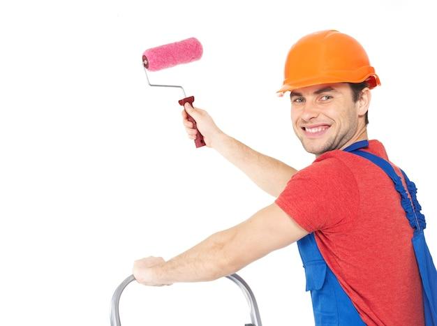 Pittore artigiano sta sulle scale con rullo, ritratto su muro bianco