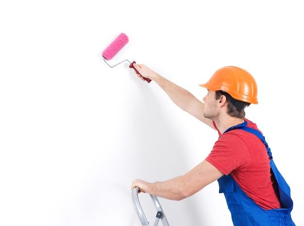 Pittore artigiano sta sulle scale con rullo, ritratto su bianco