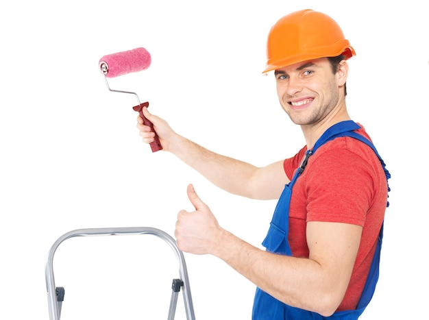 Craftsman painter stands on the stairs with roller and showing the thumbs up sign, full portrait over white background