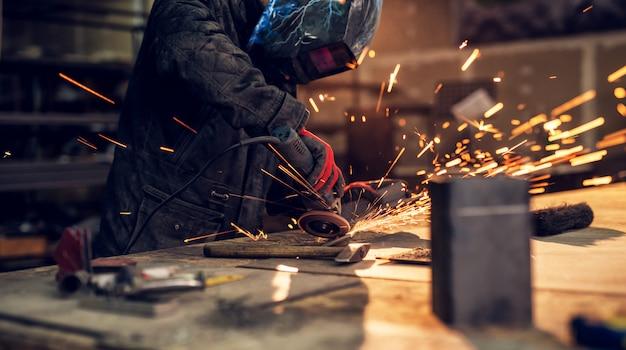Ремесленник распиливает металл, сверкает вокруг мастерской