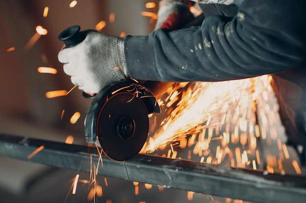 Craftsman sawing metal with disk grinder saw in workshop