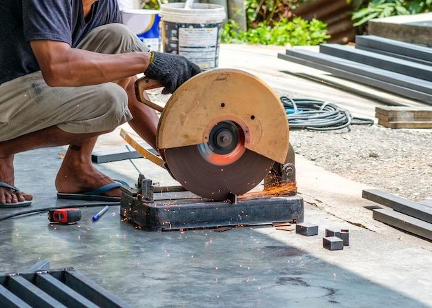 ディスクグラインダーと火花で鋼を鋸で切る職人