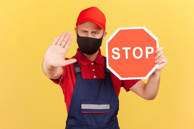 Craftsman in uniform and hygienic face mask showing stop gesture and holding red stop road sign,
