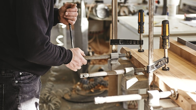 Craftsman using clamps fixate two pieces of wood and iron the process of making desk furniture