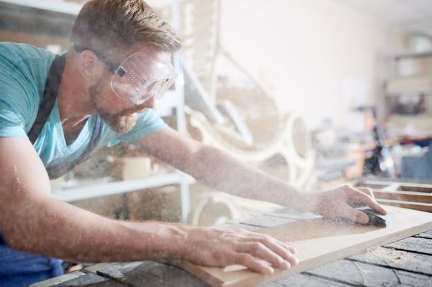 Craftsman using sandpaper