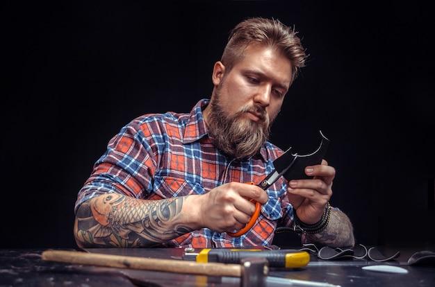 Мастер, работающий с кожей, производит изделия из кожи в кожевенном ателье.