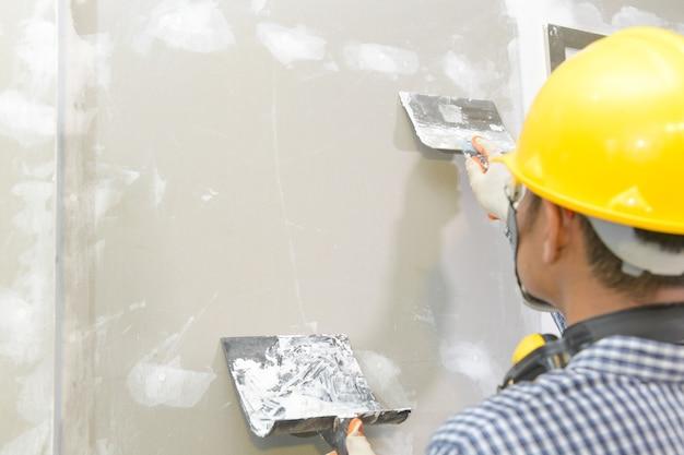 Мастер, работающий с гипсокартонным потолком в интерьере, строит гипсокартонный потолок.