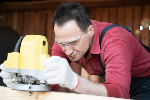Craftsman working on wooden workpiece with milling tool close up at country house workshop