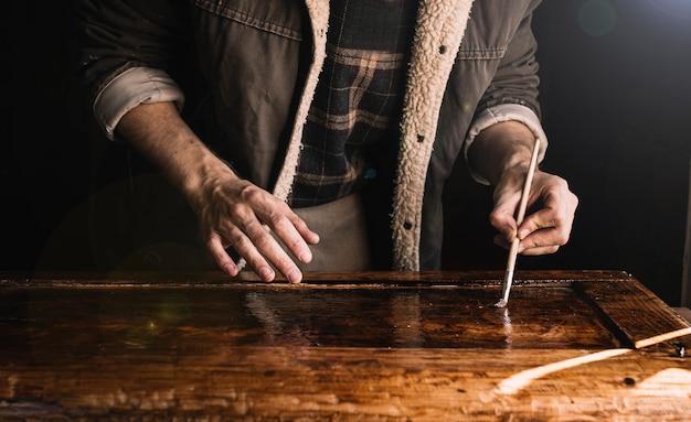 Мастер работает в мастерской с лаком по дереву деревянным элементом мебели