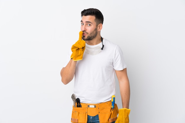 Craftsmen or electrician man over isolated white wall doing silence gesture