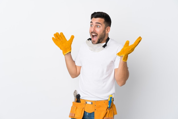 Craftsmen or electrician man over isolated white wall with surprise facial expression