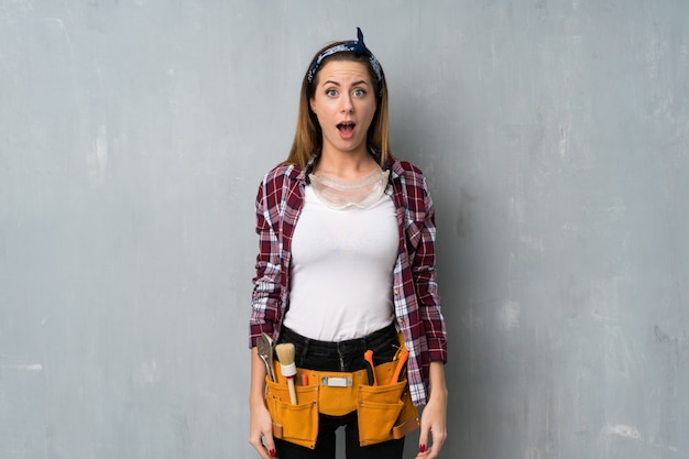 Craftsmen or electrician woman with surprise facial expression