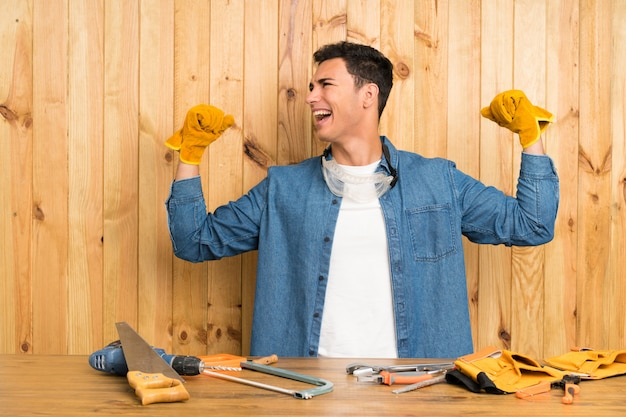Craftsmen man over wood wall celebrating a victory