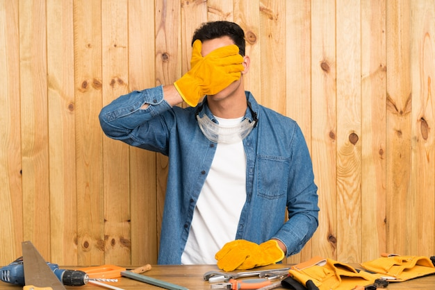 Craftsmen man over wood wall covering eyes by hands