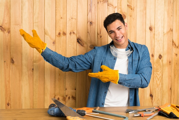 Craftsmen man over wood wall extending hands to the side for inviting to come