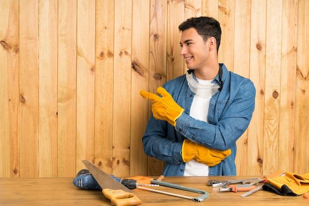 Craftsmen man over wood wall pointing finger to the side