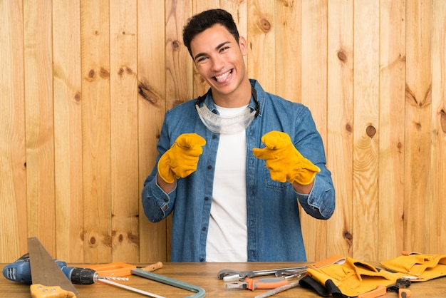 Craftsmen man over wood wall points finger at you