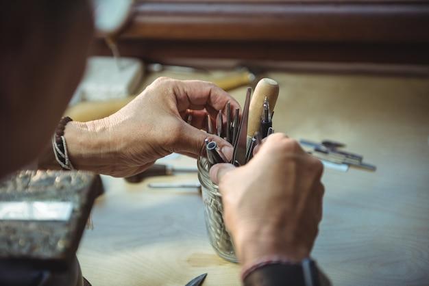 Craftswoman holding various tools