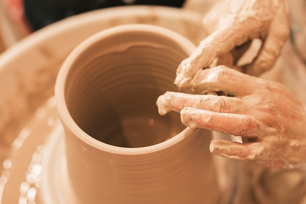Craftswoman shapes the earthen pot with his hands on pottery wheel