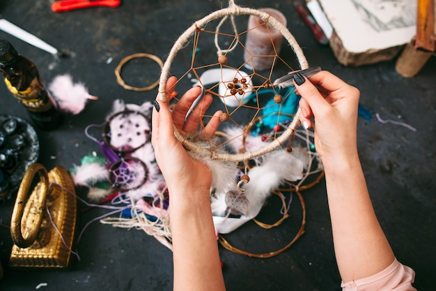 Craftswoman showing dreamcatcher in process