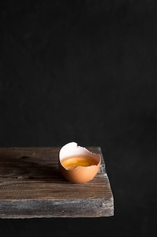 Craked egg on wooden board