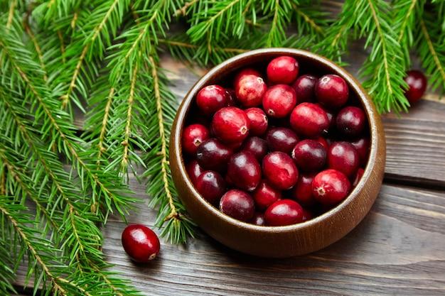 Свежие ягоды клюквы в деревянной миске на столе с ветвями елки