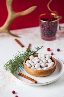 Cranberries in powdered sugar in a plate with a tube of cinnamon and a fir branch