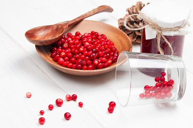 Cranberries in wooden bowl with spoon and jam in jar on white surface