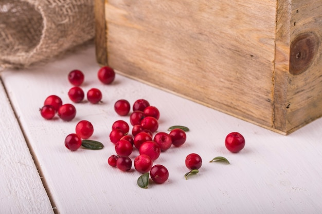 Cranberries in a wooden box and burlap on a white table