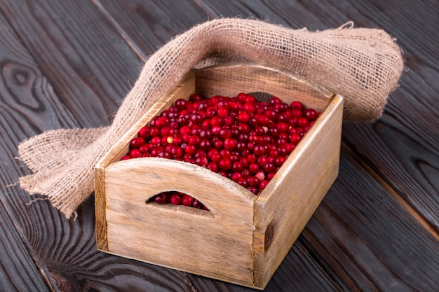 Cranberries in a wooden box and burlap on a wooden table