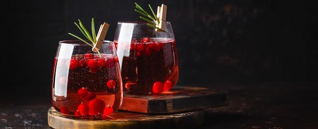 白のグラス2杯にローズマリーとクランベリーカクテル