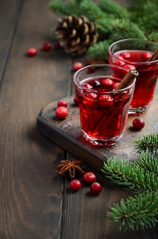 Cranberry drink on wooden decorated with fir branches, spices and fresh berries.