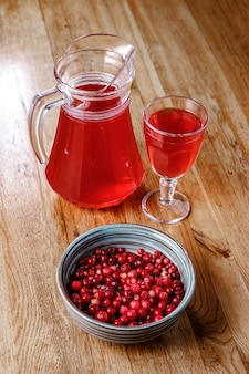 Cranberry juice in a jug on a wooden table.