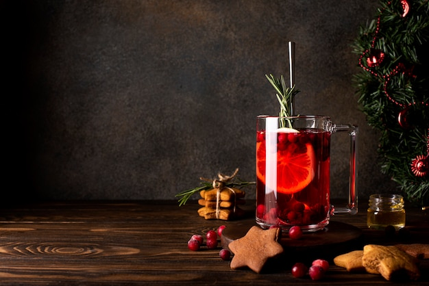 Cranberry juice with lemon honey and cinnamon in a glass mug, close-up