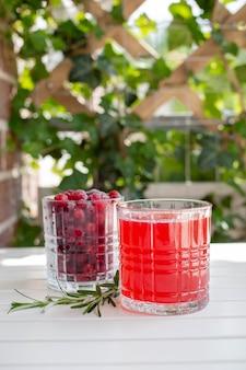 Клюквенный лимонад или сок, красный напиток со спелыми ягодами и розмарином на белом деревянном столе