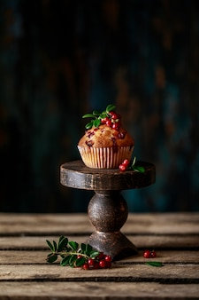 Cranberry muffins with fresh berries on rustic background