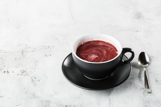 Клюква, красный или малиновый чай в темной чашке, изолированные на светлом фоне мрамора. вид сверху, копирование пространства. реклама для меню кафе. меню кафе. горизонтальное фото.