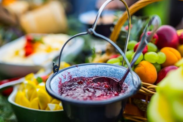 신선한 과일로 가득한 테이블에 크랜베리 소스. 야외 케이터링.