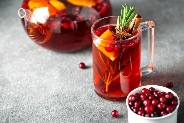 ガラスのティーポットにクランベリーティー、シナモン、オレンジ、ローズマリー、スターアニス、蜂蜜