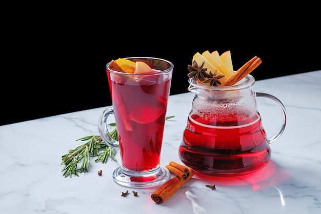 Cranberry tea with cinnamon, anise, apple and orange on marble table with copy space for text