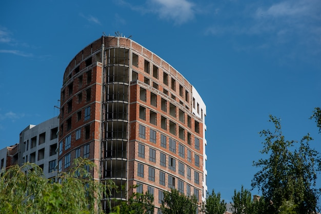 Кран и строительная площадка против голубого неба