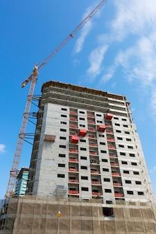 青い空を背景にクレーンと建物の建設現場