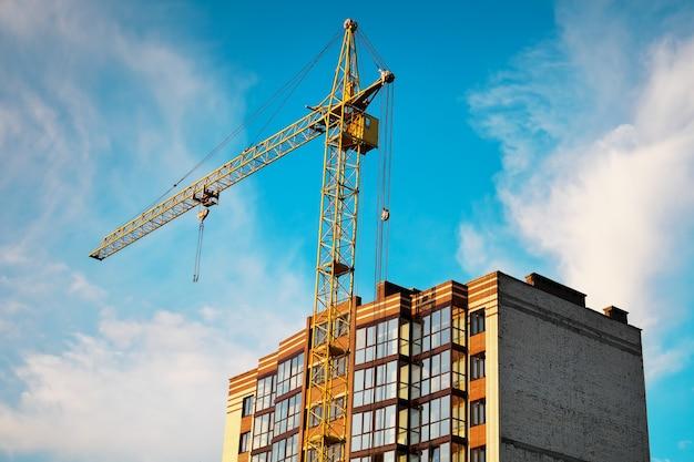 Кран и готовый дом. строительство зданий. верх здания и небо.